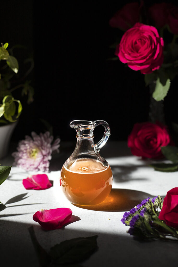 a fancy bottle of honey syrup surrounded by flowers