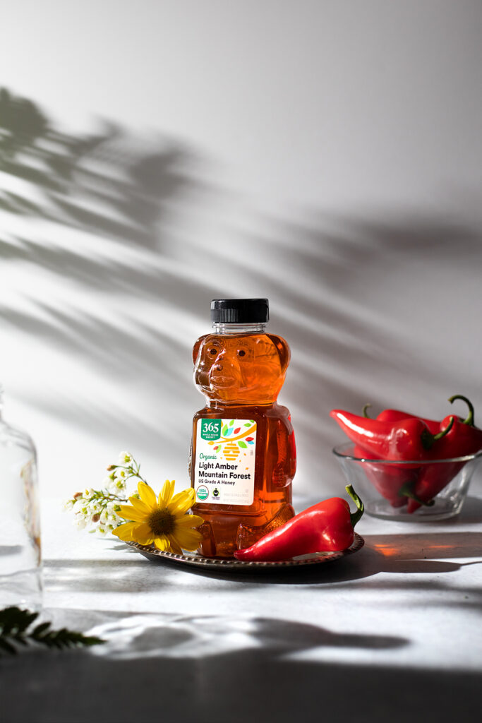 bear-shaped bottle of honey on a table in the sun