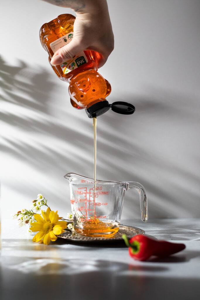 squeezing honey into a measuring cup