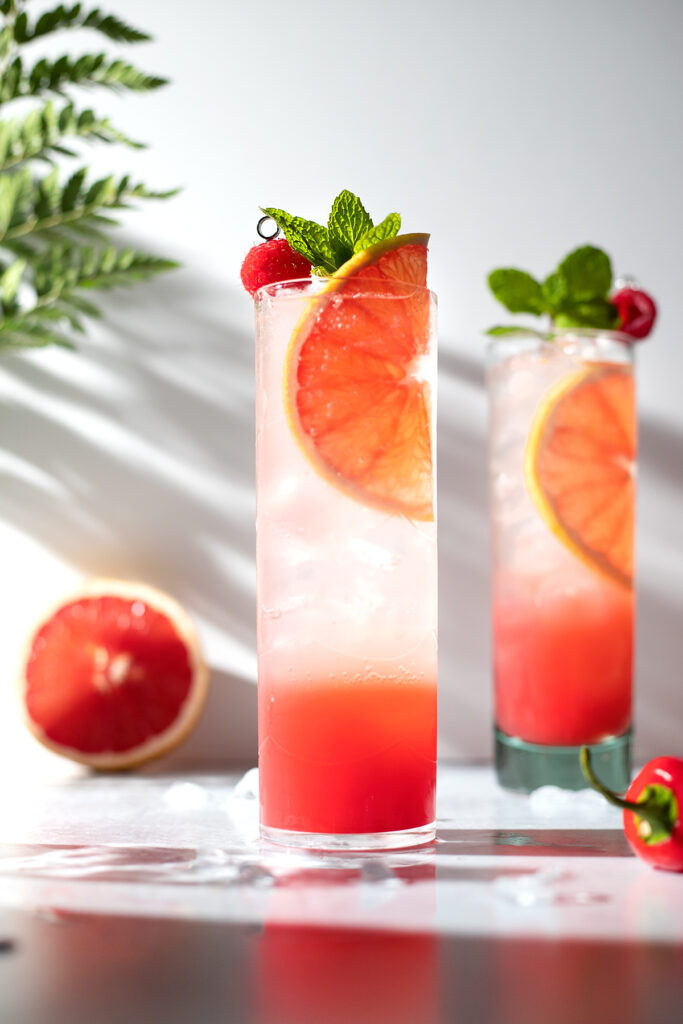 two tall glasses filled with bubbly liquid garnished with grapefruit slices and mint