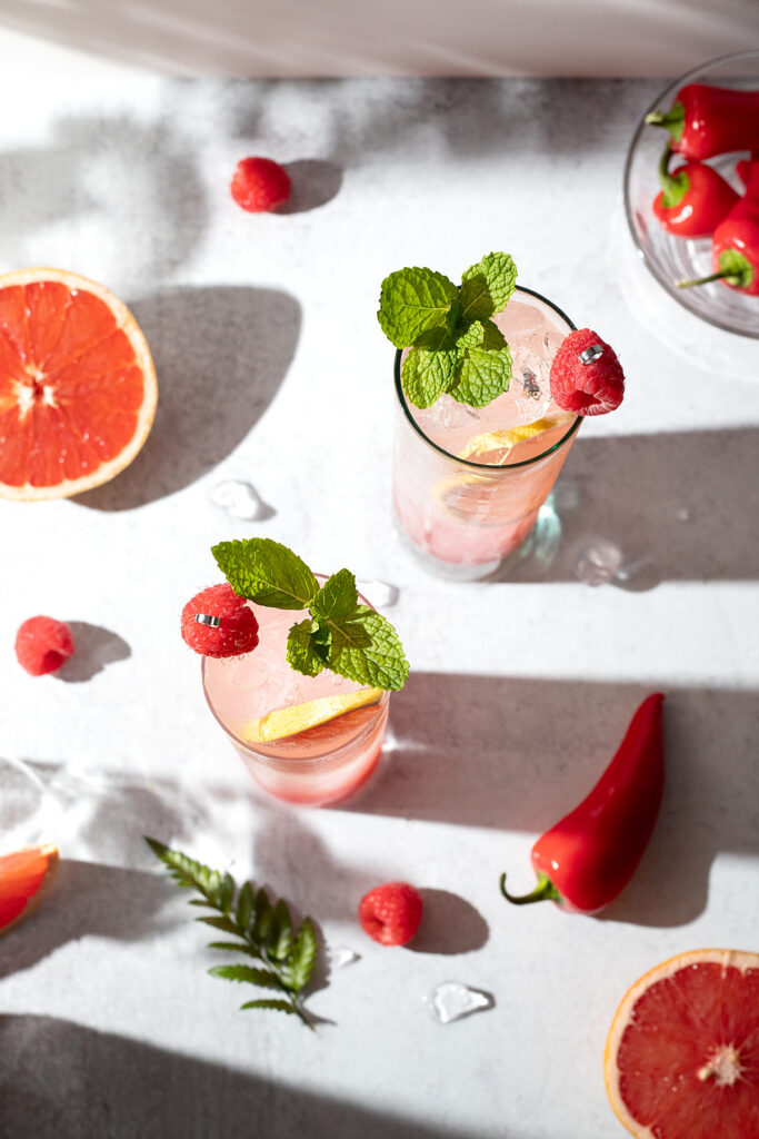 overhead view of pink bubbly drinks garnished with raspberries and mint