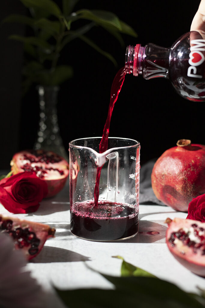 pouring pomegranate juice into a measuring cup