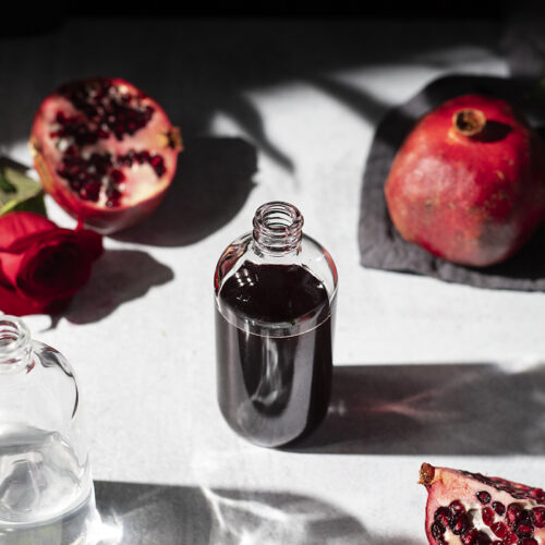 a small apothecary bottle with dark red liquid surrounded by pomegranates