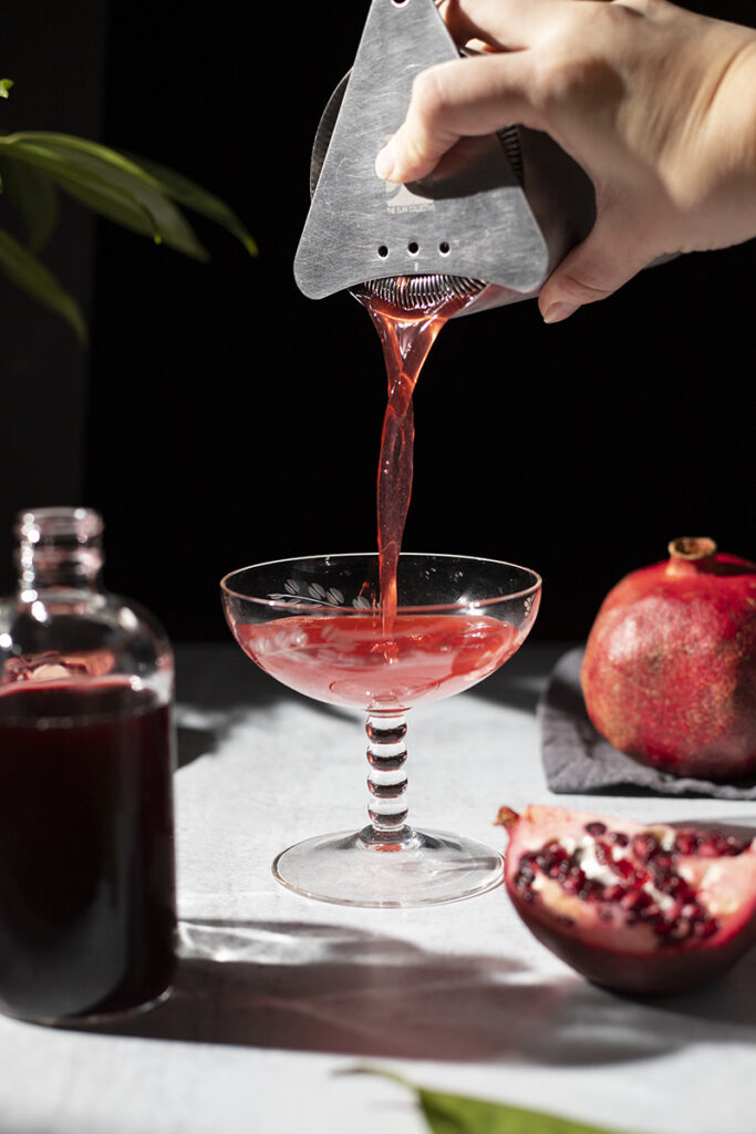 pouring a red cocktail into a coupe glass