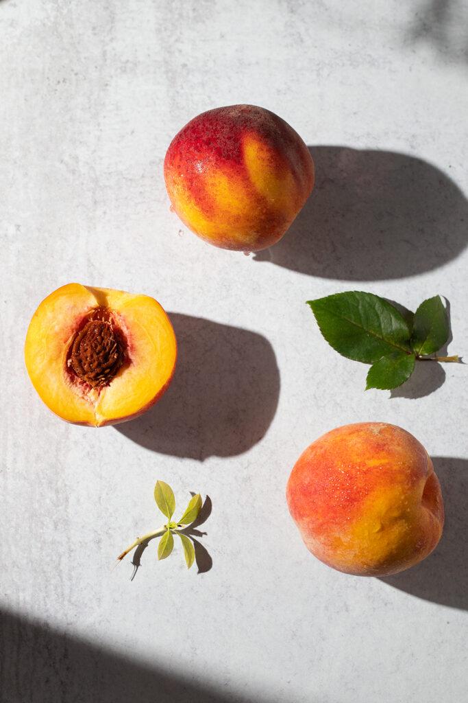 three yellow peaches on a white table.