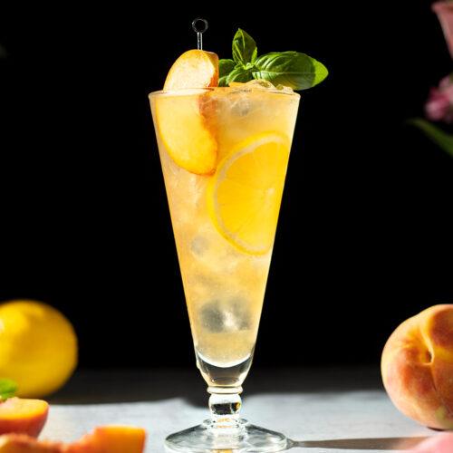 tall glass filled with peach green tea lemonade and peach slice.