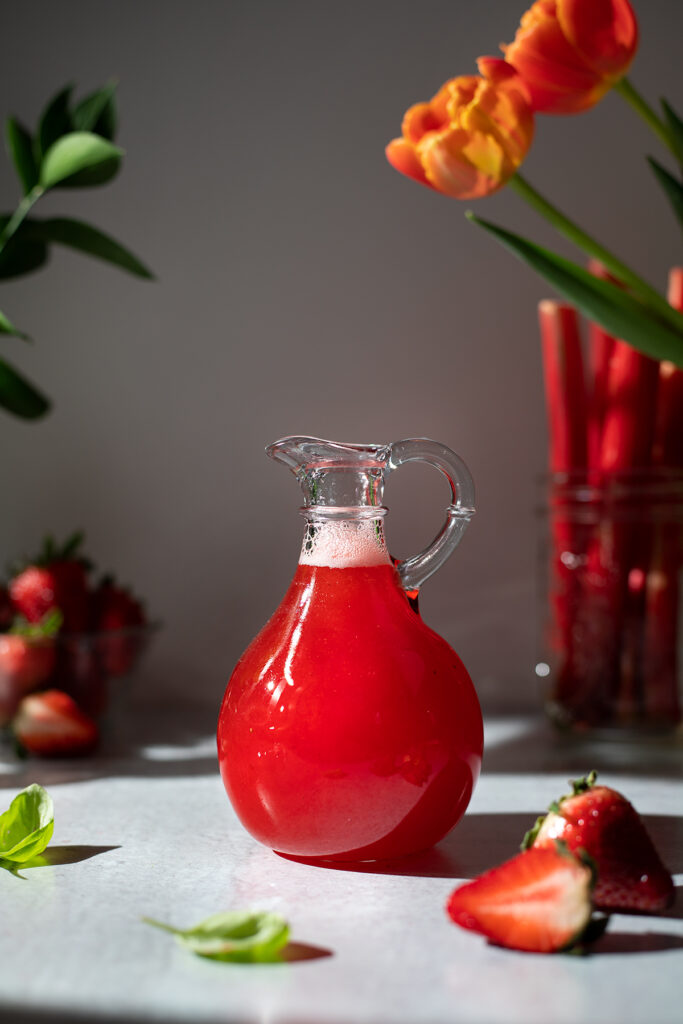 a small pitcher of bright red strawberry rhubarb syrup.