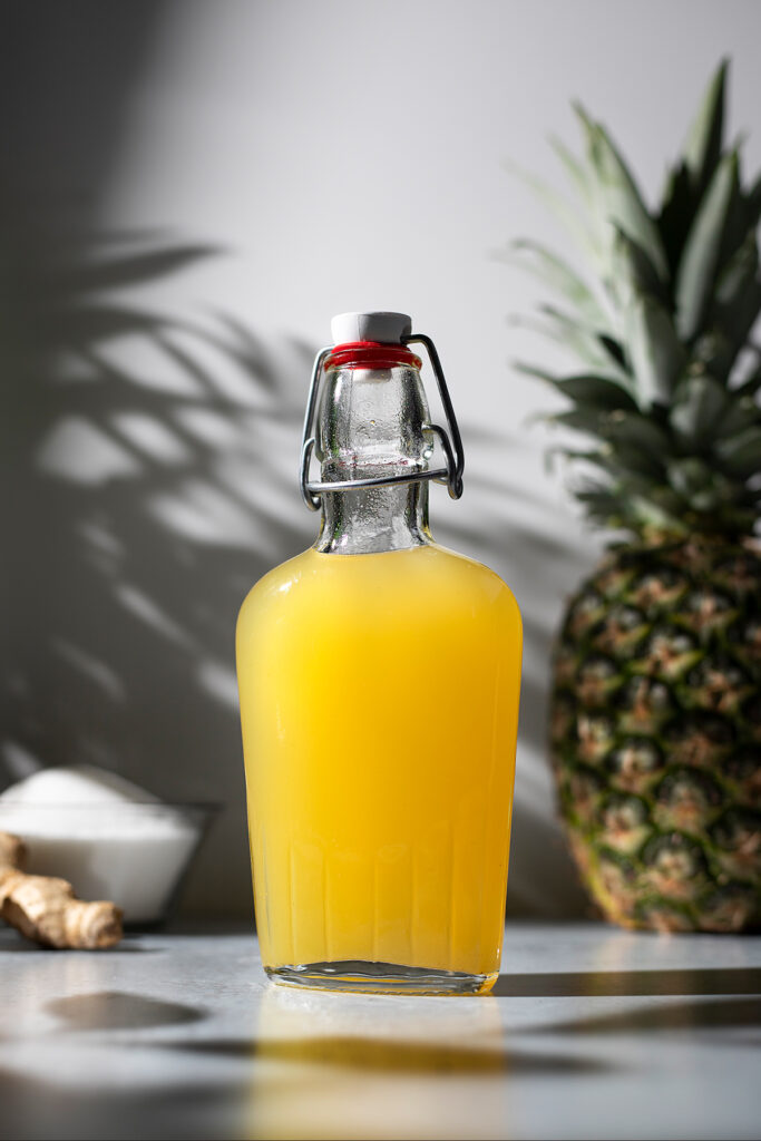 swing top bottle filled with bright yellow pineapple ginger syrup.