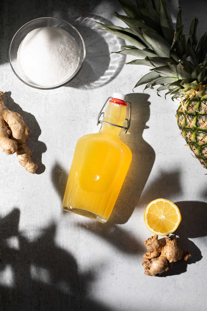 bottle of yellow syrup on a white table next to sugar, ginger, and a pineapple.