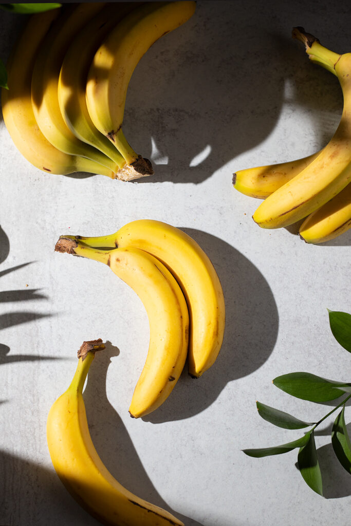 several bananas laying flat on a white table.