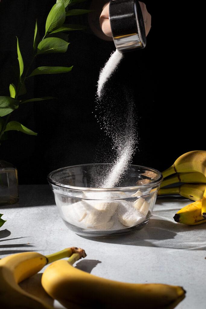 pouring sugar into a mixing bowl next to bananas.