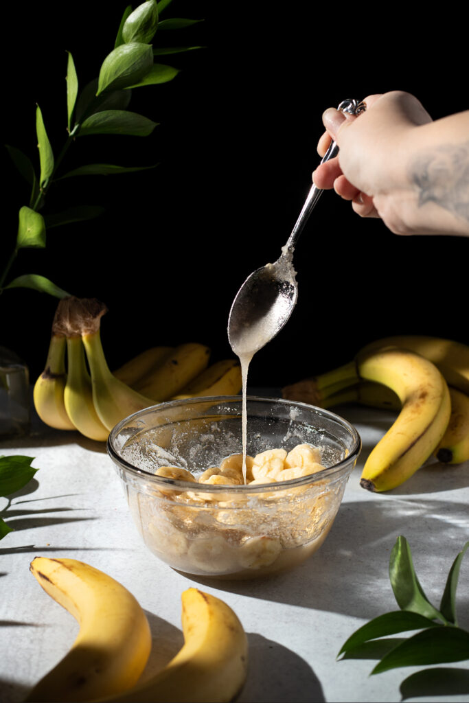 thick banana syrup dripping from a spoon into a bowl.