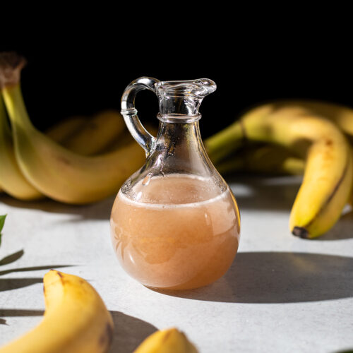 a small pitcher of thick golden brown syrup next to bananas.