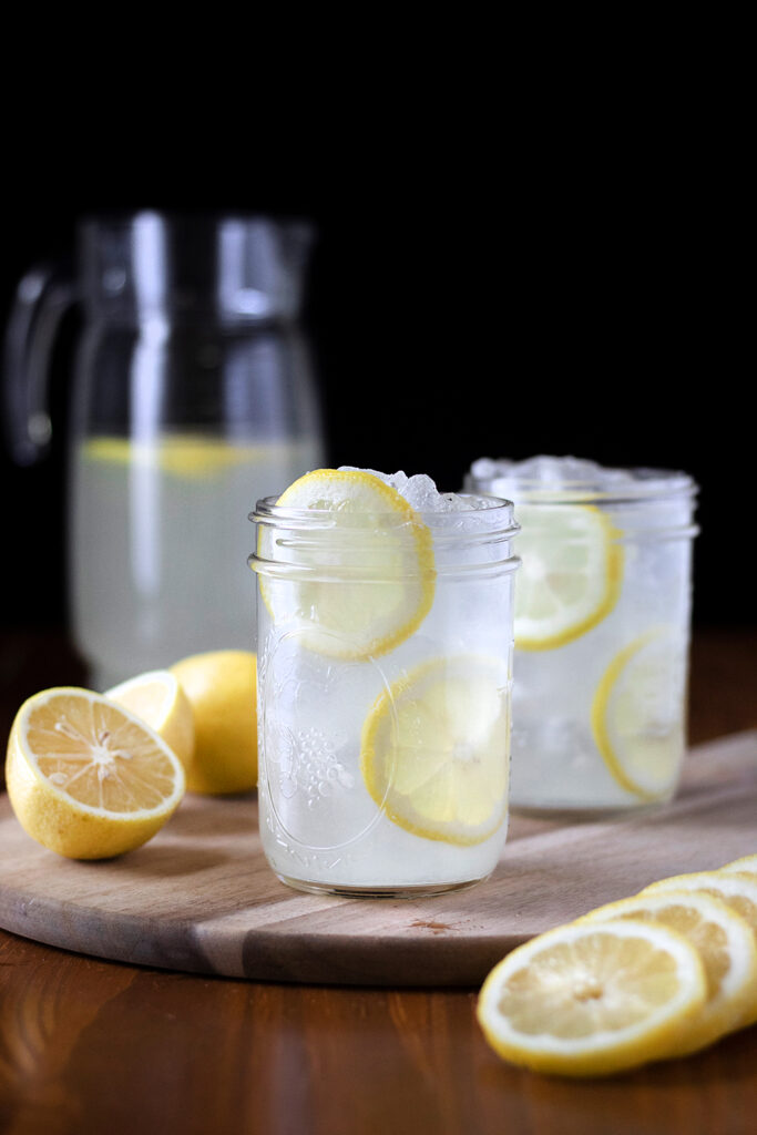 two glasses of lemonade with lemon slices and a pitcher.